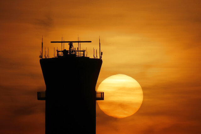 FILE - In this Tuesday, March 17, 2020 file photo, the sun sets behind the FAA Control Tower at Chicago's Midway International Airport in Chicago. Southwest Airlines has cancelled all of its fights in and out of Midway International Airport, days after federal authorities closed the airport's control tower after technicians tested positive for the coronavirus. (AP Photo/Charles Rex Arbogast, File)