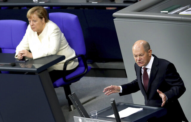 German Finance Minister Olaf Scholz, right, delivers a speech during a budget debate as part of a meeting of the German federal parliament, Bundestag, at the Reichstag building in Berlin, Germany, Tuesday, Sept. 29, 2020. At left is German Chancellor Angela Merkel. (AP Photo/Michael Sohn)
