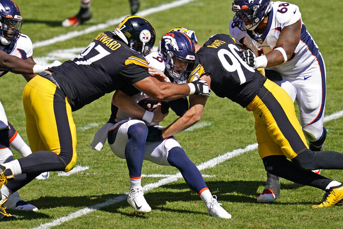 Denver Broncos quarterback Jeff Driskel (9) is sacked by Pittsburgh Steelers defensive tackle Cameron Heyward (97) and T.J. Watt (90) during the first half of an NFL football game, Sunday, Sept. 20, 2020, in Pittsburgh. (AP Photo/Keith Srakocic)