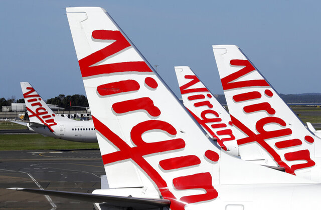 Virgin Australia planes are lined up at departure gates at Sydney Airport in Sydney, Wednesday, April 22, 2020. Virgin Australia is seeking bankruptcy protection, entering voluntary administration after a debt crisis worsened by the coronavirus shutdown pushed it into insolvency. (AP Photo/Rick Rycroft)