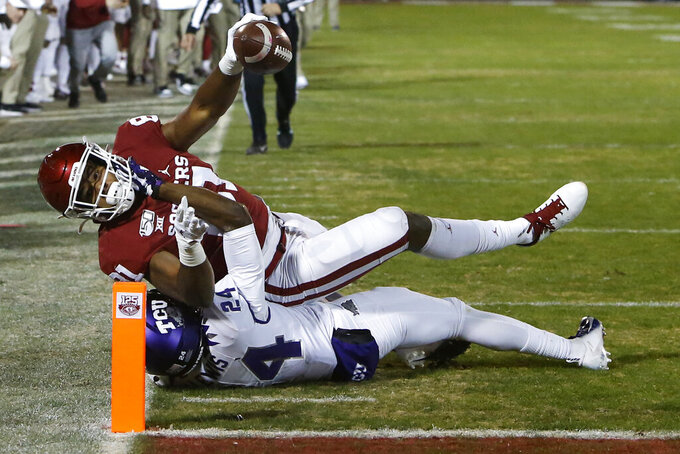 Oklahoma fullback Brayden Willis (81) reaches the ball into the end zone for a touchdown as he is tackled by TCU cornerback Julius Lewis (24) in the first half of an NCAA college football game in Norman, Okla., Saturday, Nov. 23, 2019. (AP Photo/Sue Ogrocki)