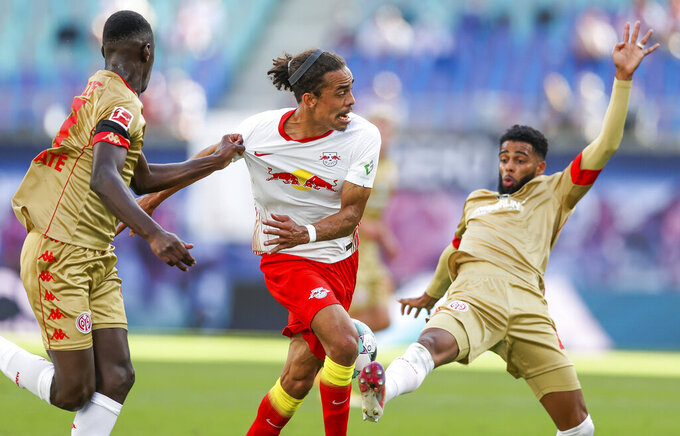 Leipzig's Yussuf Poulsen, center, battles for the ball with Moussa Niakhate, left, and Jeremiah St. Juste from Mainz during a German Bundesliga soccer match between RB Leipzig and FSV Mainz 05 in Leipzig, Germany, Sunday, Sept. 20, 2020. (Jan Woitas/dpa via AP)