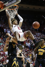 Indiana guard Romeo Langford (0) hangs from the rim after dunking over Iowa forward Luka Garza in the second half of an NCAA college basketball game in Bloomington, Ind., Thursday, Feb. 7, 2019. Iowa won 77-72. (AP Photo/AJ Mast)