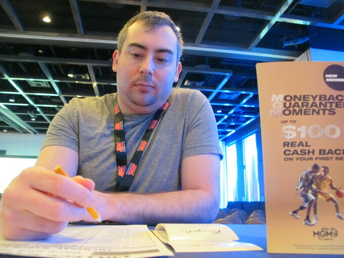Mike Heusser, of Middletown, Conn., checks off bets he planned to make on the NCAA basketball tournament, Thursday, March 21, 2019, at the Borgata casino in Atlantic City. College basketball fans are lining up at casinos and racetracks, and furiously tapping smartphone screens to get down bets on the March Madness college basketball tournament, in many states where it is legal for the first time. (AP Photo/Wayne Parry)