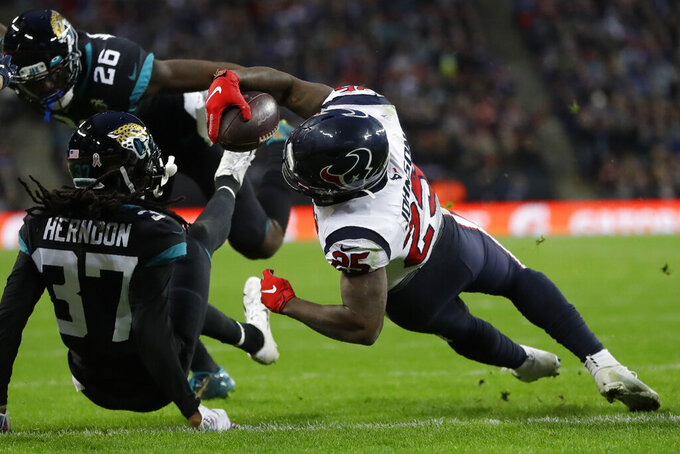 Houston Texans running back Duke Johnson (25) dives into the end zone for a touchdown against Jacksonville Jaguars cornerback Tre Herndon (37) during the second half of an NFL football game at Wembley Stadium, Sunday, Nov. 3, 2019, in London. (AP Photo/Kirsty Wigglesworth)