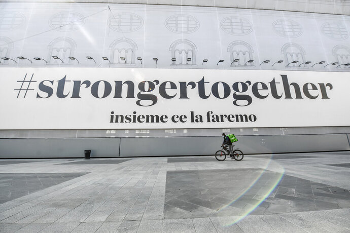 A food delivery rider passes by a banner reading ' Stronger together, all together we will make it ',  in Milan, Italy, Sunday, April 5, 2020. The government is demanding Italians stay home and not take the leveling off of new coronavirus infections as a sign the emergency is over, following evidence that more and more Italians are relaxing restrictions the west's first and most extreme nationwide lockdown and production shutdown. (Claudio Furlan/LaPresse via AP)