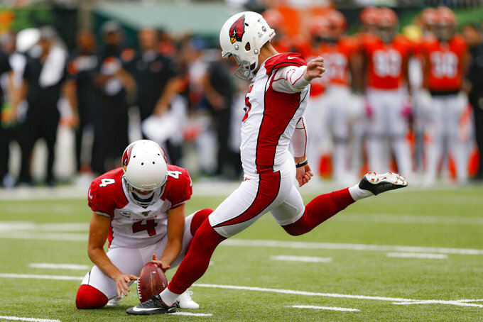 Arizona Cardinals kicker Zane Gonzalez (5) boots an extra point alongside placeholder Andy Lee (4) in the first half of an NFL football game against the Cincinnati Bengals, Sunday, Oct. 6, 2019, in Cincinnati. (AP Photo/Gary Landers)
