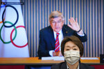 """FILE - In this April 28, 2021, file photo, IOC President Thomas Bach, on a screen, waves to Tokyo 2020 Organizing Committee President Seiko Hashimoto at the start of a five-party meeting of Tokyo 2020 Olympic and Paralympic Games in Tokyo. Bach has canceled a trip in May 2021 to Japan because of surging cases of COVID-19 in the country, the Tokyo Olympic organizing committee said Monday, May 10, 2021 in a statement. Hashimoto said last week that the trip would be """"tough"""" for Bach to make, which was interpreted in Japan as meaning it was canceled. (Franck Robichon/Pool Photo via AP, File)"""