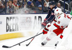 Columbus Blue Jackets' Vladislav Gavrikov, rear, of Russia, and Carolina Hurricanes' Warren Foegele chase the puck during the first period of an NHL hockey game Thursday, Jan. 16, 2020, in Columbus, Ohio. (AP Photo/Jay LaPrete)