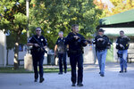 Santa Rosa police officers carry guns as they search the campus of Ridgway High School for suspects after a shooting at the school in Santa Rosa, Calif., Tuesday, Oct. 22, 2019. (Beth Schlanker/The Press Democrat via AP)