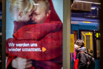 A pupil waits for a subway train in Frankfurt, Germany, Wednesday, Nov. 25, 2020. The German government will discuss further restrictions to avoid the outspread of the coronavirus. Letters on a an advertise read