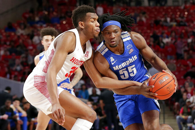 Houston forward Fabian White Jr. (35) reaches in as Memphis forward Precious Achiuwa (55) drives to the basket during the first half of an NCAA college basketball game Sunday, March 8, 2020, in Houston. (AP Photo/Michael Wyke)
