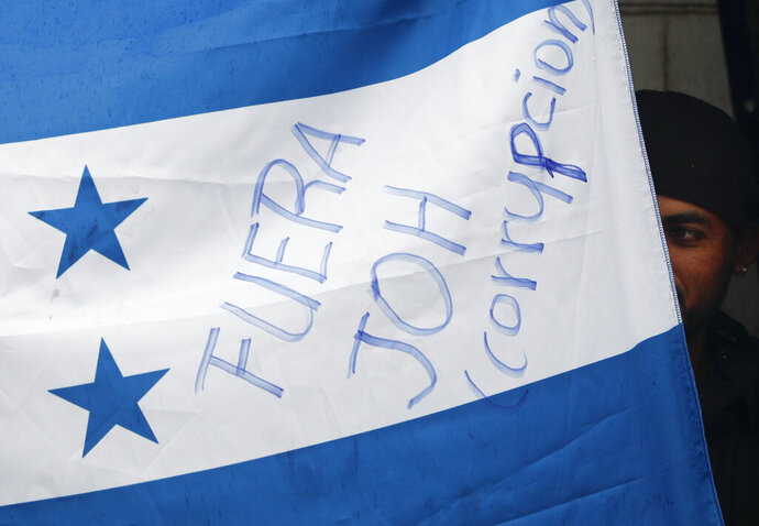 FILE - In this Dec. 6, 2018 file photo, a Honduran migrant emergences from a sleeping area behind a Honduran flag printed with a slogan calling on Honduras' President Juan Orlando Hernandez, commonly called JOH, to leave office because of corruption, inside the Barretal migrant shelter in Tijuana, Mexico. The brutal Oct. 26, 2019 murder of an alleged Honduran drug trafficker with a potentially critical piece of evidence against the president has the Central American government pointing the finger at other drug traffickers for his death, while the man's lawyers suggest the government may have been responsible. The ledgers included entries logging cocaine shipments for Hernández, a former Honduran congressman, and the initials of his brother, President Juan Orlando Hernández, who is known throughout Honduras as JOH. The president has denied any wrongdoing and has not been charged. (AP Photo/Rebecca Blackwell, File)