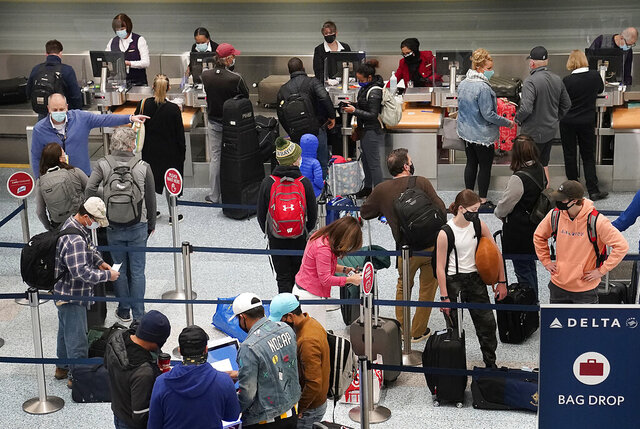 Holiday travelers crowd the ticketing area of terminal one Wednesday, Nov. 25, 2020 at MSP in Minneapolis. Millions of Americans took to the skies and the highways ahead of Thanksgiving at the risk of pouring gasoline on the coronavirus fire, disregarding increasingly dire warnings that they stay home and limit their holiday gatherings to members of their own household. (David Joles/Star Tribune via AP)