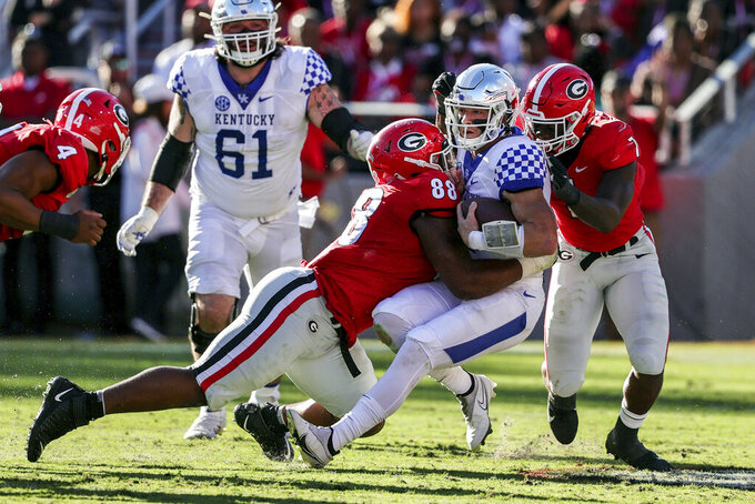 Kentucky quarterback Will Levis (7) is sacked by Georgia defensive lineman Jalen Carter (88) and linebacker Quay Walker (7) during the first half of an NCAA college football game Saturday, Oct. 16, 2021 in Athens, Ga. (AP Photo/Butch Dill)