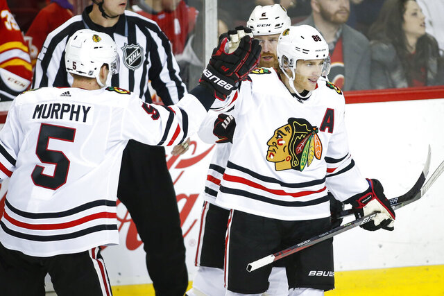Chicago Blackhawks' Patrick Kane, right, celebrates his goal with teammates Duncan Keith, center, and Connor Murphy during the first period of an NHL hockey game against the Calgary Flames on Tuesday, Dec. 31, 2019, in Calgary, Alberta. (Jeff McIntosh/The Canadian Press via AP)