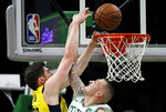 Boston Celtics forward Daniel Theis, right, fouls Indiana Pacers forward T.J. Leaf, left, on a slam dunk during the first quarter of an NBA basketball game in Boston, Wednesday, Jan. 9, 2019. (AP Photo/Charles Krupa)
