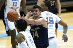 Notre Dame forward Nate Laszewski (14) drives to the basket while North Carolina forward Garrison Brooks (15) and guard Caleb Love (2) defend during the second half of an NCAA college basketball game in Chapel Hill, N.C., Saturday, Jan. 2, 2021. (AP Photo/Gerry Broome)