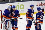 New York Islanders goaltender Thomas Greiss (1) celebrates with teammates Mathew Barzal (13), Jordan Eberle (7) and Anders Lee (27) during the third period of an NHL hockey game Tuesday, Jan. 14, 2020, in Uniondale, N.Y. The Islanders won 8-2. (AP Photo/Frank Franklin II)