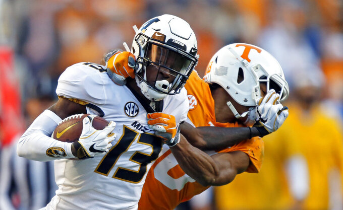 Missouri wide receiver Kam Scott (13) tries to escape the grasp of Tennessee defensive back Nigel Warrior (18) in the first half of an NCAA college football game Saturday, Nov. 17, 2018, in Knoxville, Tenn. (AP Photo/Wade Payne)