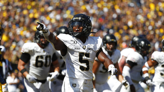 Army running back Kell Walker (5) points after a Kelvin Hopkins Jr. touchdown in the first half of an NCAA college football game against Michigan in Ann Arbor, Mich., Saturday, Sept. 7, 2019. (AP Photo/Paul Sancya)