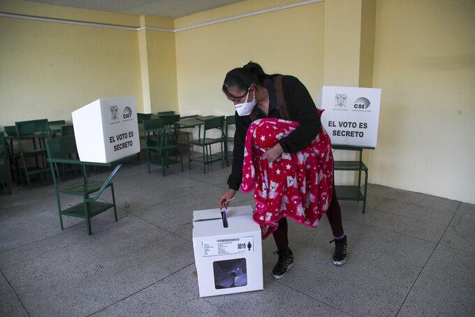 A woman votes during a runoff presidential election in Quito, Ecuador, Sunday, April 11, 2021. (AP Photo/Dolores Ochoa)