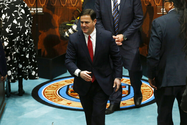 File - In this Jan. 13, 2020, file photo, Arizona Republican Gov. Doug Ducey exits the House of Representatives floor after delivering his State of the State address on the opening day of the legislative session at the Capitol in Phoenix. Ducey spent years opposing divisive anti-immigration legislation, then embraced it this year before being forced to backtrack after business groups revolted. The Republican governor and GOP legislative leaders pulled a proposal to put an existing sanctuary city ban in the state constitution late Thursday, Feb. 20.  (AP Photo/Ross D. Franklin, File)