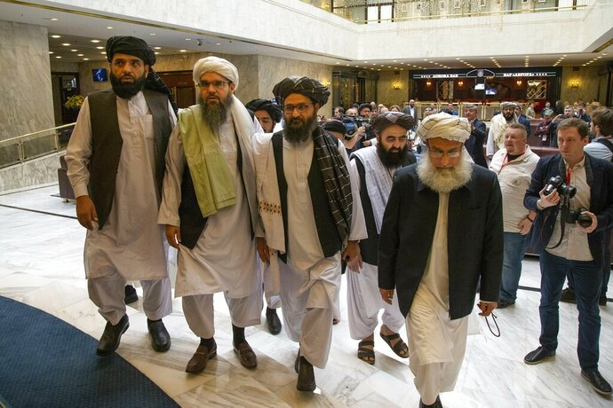 FILE - In this May 28, 2019 file photo, Mullah Abdul Ghani Baradar, the Taliban group's top political leader, third from left, arrives with other members of the Taliban delegation for talks in Moscow, Russia. The Taliban said Tuesday, Oct. 22, 2019, that a fresh round of intra-Afghan peace talks is to be held in China next week. The announcement raises hopes for renewed negotiations, even as violence surges in Afghanistan's 18-year war. Suhail Shaheen, spokesman for the Taliban's political office in Qatar, said Tuesday that the talks are planned for Oct. 28 and 29. (AP Photo/Alexander Zemlianichenko, File)