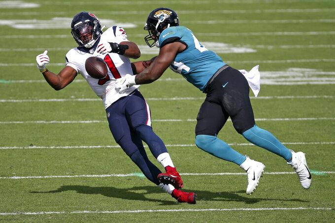Jacksonville Jaguars linebacker Myles Jack, right, breaks up a pass intended for Houston Texans running back David Johnson, left, during the first half of an NFL football game, Sunday, Nov. 8, 2020, in Jacksonville, Fla. (AP Photo/Stephen B. Morton)