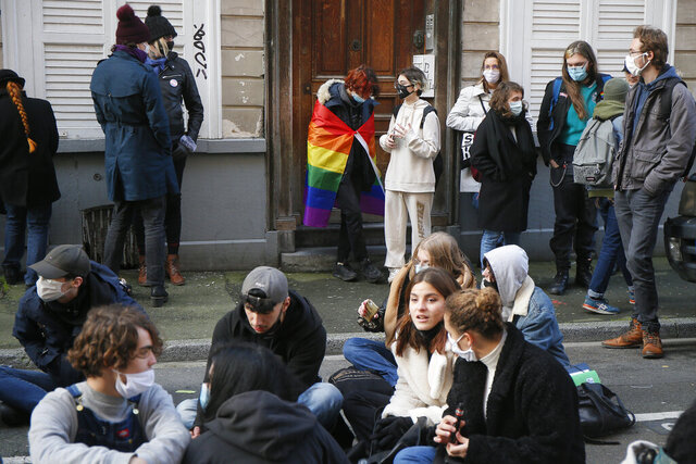Students stage a sit-in outside the Fenelon High School in Lille, northern France, Friday, Dec. 18, 2020. About 100 teenagers rallied in northern France to pay homage to a transgender student who killed herself this week after facing tensions with school officials around her gender identity. (AP Photo/Michel Spingler)