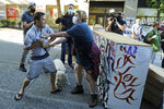 A person tries to take away a hammer from a man at left who was using it to remove artwork on barricades Friday, June 26, 2020 at the CHOP (Capitol Hill Occupied Protest) zone in Seattle. The man lives in a house in the same block and said he was tired of protesters occupying his neighborhood. Also on Friday Seattle Department of Transportation workers arrived with the intention of removing barricades that had been set up in the area, but left after being met with resistance from protesters. (AP Photo/Ted S. Warren)