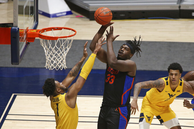 Florida center Jason Jitoboh (33) shoots while defended by West Virginia forward Derek Culver (1) during the second half of an NCAA college basketball game Saturday, Jan. 30, 2021, in Morgantown, W.Va. (AP Photo/Kathleen Batten)