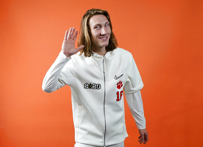 FILE - In this Jan. 11, 2020, filephoto, Clemson quarterback Trevor Lawrence poses during media day for the NCAA College Football Playoff national championship game, in New Orleans. Clemson is preseason No. 1 in The Associated Press Top 25, Monday, Aug. 24, 2020, a poll featuring nine Big Ten and Pac-12 teams that gives a glimpse at what's already been taken from an uncertain college football fall by the pandemic. (AP Photo/David J. Phillip, File)