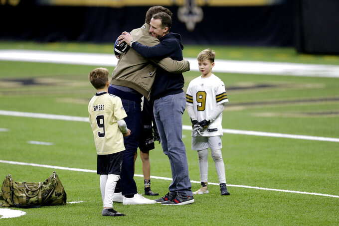 New Orleans Saints quarterback Drew Brees right, speaks with Tampa Bay Buccaneers quarterback Tom Brady as Bree's children look on after an NFL divisional round playoff football game between the New Orleans Saints and the Tampa Bay Buccaneers, Sunday, Jan. 17, 2021, in New Orleans. The Tampa Bay Buccaneers won 30-20. (AP Photo/Brett Duke)