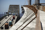FILE - In this July 2, 2018, file photo, traffic moves on the old Gerald Desmond Bridge next to its replacement bridge under construction in Long Beach, Calif. President Donald Trump's tariffs are taxes paid by American importers and are typically passed along to their customers. They can provoke retaliatory tariffs on U.S. exports. (AP Photo/Jae C. Hong, File)