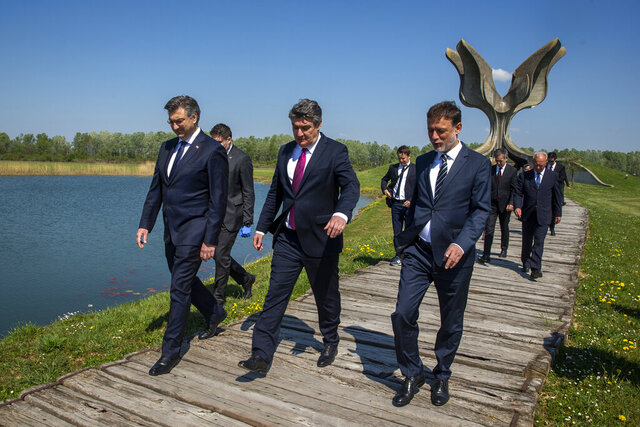 Croatia's President Zoran Milanovic, center, Prime Minister Andrej Plenkovic, left, and Parliament speaker Gordan Jandrokovic walk away from the monument after laying flowers during a commemoration ceremony for the victims of a World War II camp in Jasenovac, Croatia, Wednesday, April 22, 2020. Representatives of the Croatian Jews, Serbs, Roma and anti-fascists for the first time in years agreed to join top Croatian officials at the ceremony, but warned this was because of the emergency situation over the new coronavirus and could change unless the authorities do more to curb right-wing sentiments in the country. (AP Photo/Darko Bandic)