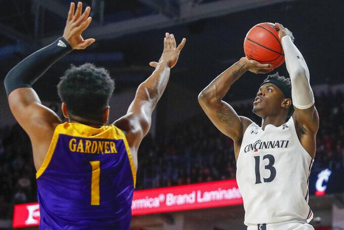 Cincinnati's Tre Scott (13) shoots over East Carolina's Jayden Gardner (1) during the first half of an NCAA college basketball game, Sunday, Jan. 19, 2020, in Cincinnati. (AP Photo/John Minchillo)