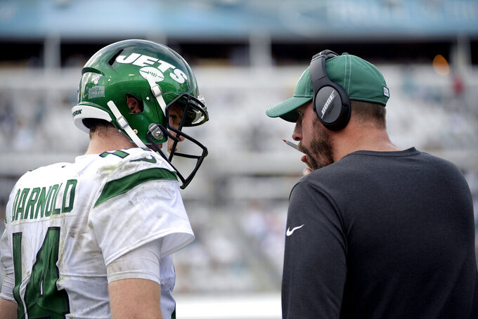 FILE - In this Oct. 27, 2019, file photo, New York Jets head coach Adam Gase, right, talks to quarterback Sam Darnold (14) on the sideline during the second half of an NFL football game against the Jacksonville Jaguars in Jacksonville, Fla. Gase sees — and hears — a clear difference in Darnold each time he opens his mouth. The Jets coach will start calling a play during practice, and the quarterback routinely finishes his sentences. (AP Photo/Phelan M. Ebenhack, File)