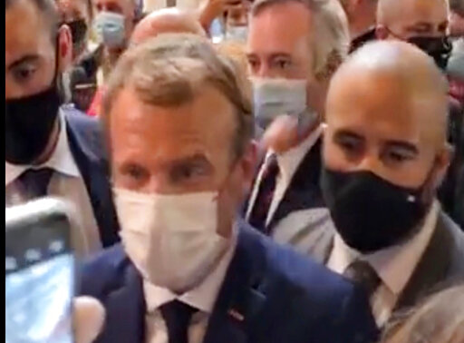 This image from video made available by Lyonmag.com shows an egg thrown toward French President Emmanuel Macron, left, to hit him on the shoulder as he walks through the restaurant trade fair in Lyon, France, Monday Sept. 27, 2021. Macron was visiting the International Catering, Hotel and Food Trade Fair to promote French gastronomy. (LYONMAG.COM via AP)