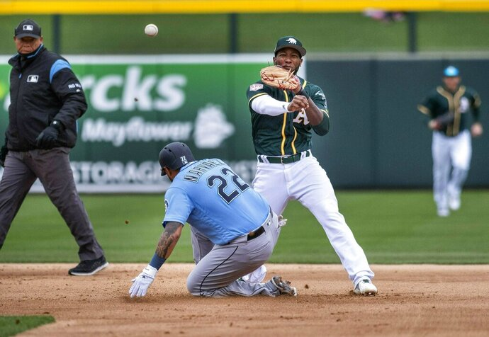 Oakland Athletics second baseman Jurdickson Profar, center right, turns a double play against Seattle Mariners' Omar Narvaez, center left, and getting Ryon Healy at first to end the top of the first inning of the first spring training baseball game of the season Thursday, Feb. 21, 2019, in Mesa, Ariz. (Dean Rutz/The Seattle Times via AP)