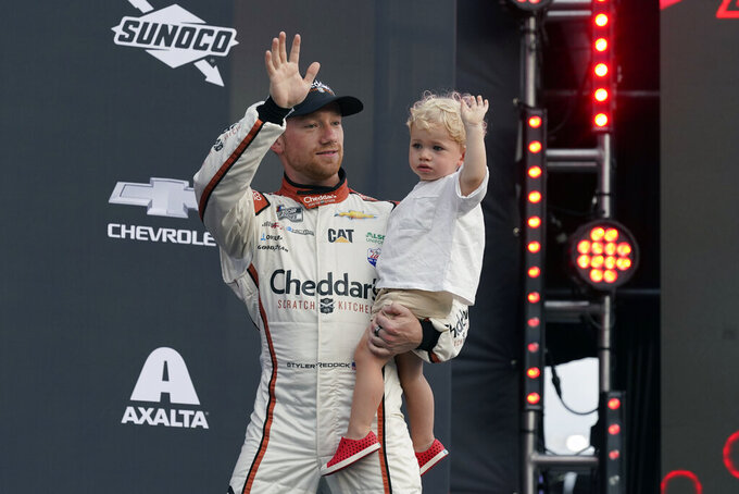 Tyler Reddick and his son Beau wave to fans during driver introductions before the NASCAR Cup Series auto race at Daytona International Speedway, Saturday, Aug. 28, 2021, in Daytona Beach, Fla. (AP Photo/John Raoux)