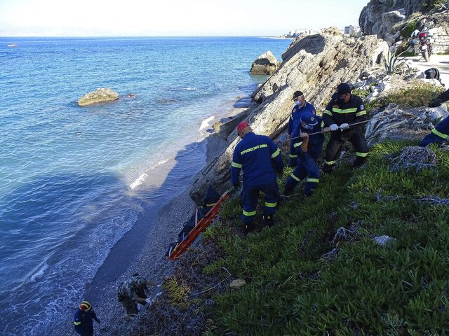 Firefighters retrieve the body of a migrant from the beach after a shipwreck on the island of Rhodes, southeastern Greece, Monday, Nov. 23, 2020. Greece's coast guard says a speedboat that appeared to have been smuggling migrants to the island of Rhodes from nearby Turkey partially sank before reaching land Monday, leaving one person dead. (Argyris Mantikos/Eurokinissi via AP)