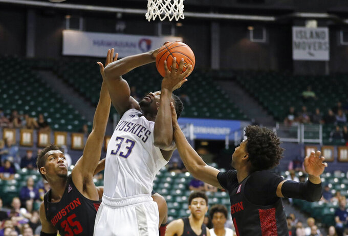 Houston guard Nate Hinton (11) fouls Washington forward Isaiah Stewart (33) during the second half of an NCAA college basketball game Wednesday, Dec. 25, 2019, in Honolulu. Stewart scored on the play. (AP Photo/Marco Garcia)