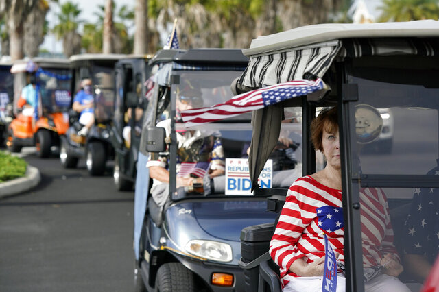 Carts line up before a parade of over 300 golf carts supporting Democratic presidential candidate former Vice President Joe Biden caravanned to the Sumter County Elections office drop off their ballots Wednesday, Oct. 7, 2020, in The Villages, Fla. (AP Photo/John Raoux)