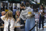 A waitress wears a mask as she serves customers dinning out in London, Monday, Sept. 21, 2020. Britain's top medical advisers have painted a grim picture of exponential growth in illness and death if nothing is done to control the second wave of coronavirus infections, laying the groundwork for the government to announce new restrictions later this week. (AP Photo/Kirsty Wigglesworth)