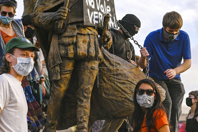 Protesters attach a chain to a statue of Spanish conquerer Juan de Oñate in Albuquerque, N.M., Monday, June 15, 2020. One man was shot during an exchange between protesters and armed members of the New Mexico Civil Guard, a civilian group trying to protect the monument. (Anthony Jackson/The Albuquerque Journal via AP)