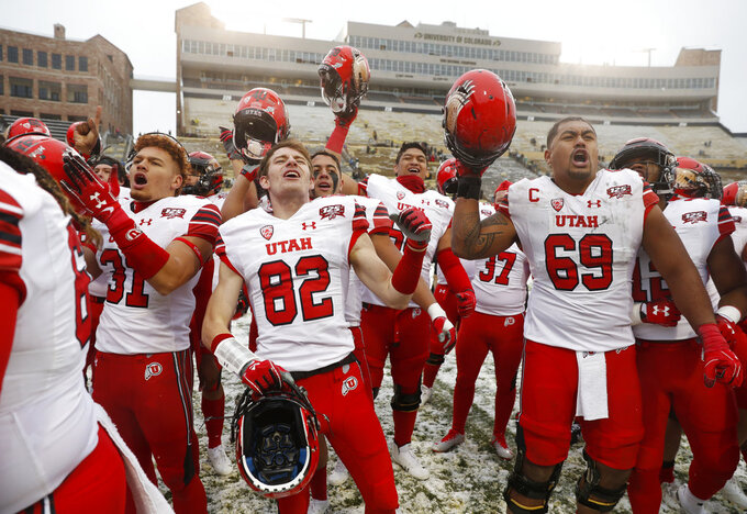 From left, Utah defensive back Keala Santiago, wide receiver Dylan Slavens and offensive lineman Lo Falemaka sing the school song with fans after an NCAA college football game against Colorado, Saturday, Nov. 17, 2018, in Boulder, Colo. Utah won 30-7. (AP Photo/David Zalubowski)