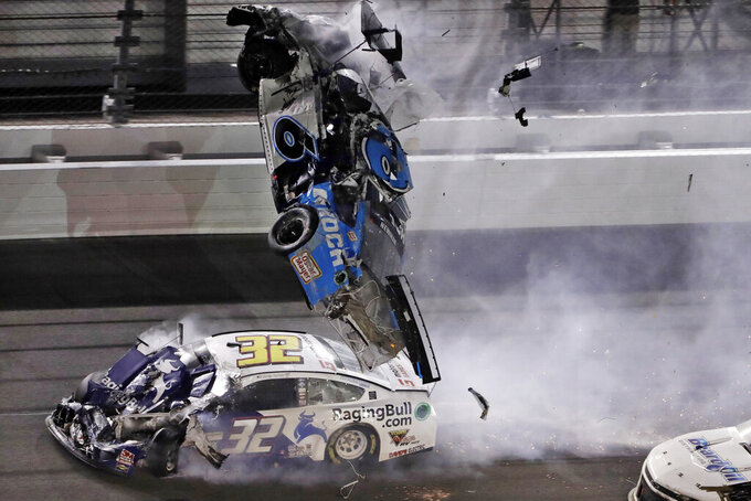 FILE - In this Feb. 17, 2020, file photo, Ryan Newman's car goes airborne after crashing into Corey LaJoie (32) during the NASCAR Daytona 500 auto race at Daytona International Speedway in Daytona Beach, Fla. NASCAR fans and fellow competitors feared the worst for Newman, but the 2008 Daytona 500 winner walked out of the hospital 48 hours later holding hands with his girls. He is a symbol of how far the sport has come since NASCAR's darkest day 20 years ago, when seven-time champion Dale Earnhardt was killed in the final turn of the 500. (AP Photo/Chris O'Meara, File)