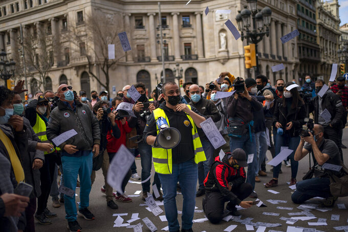 Taxi drivers throw fake money in the air during a protest in Barcelona downtown, Spain, Thursday, March 18, 2021. Hundreds of yellow-and-black cabs disrupted Barcelona's road traffic on Thursday to protest against the return of the ride-hailing giant Uber to the northeastern city after a 2-year hiatus. (AP Photo/Emilio Morenatti)