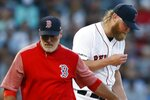 Boston Red Sox pitching coach Dana LeVangie, left, leaves the mound after speaking with Andrew Cashner during the third inning of the team's baseball game against the Toronto Blue Jays in Boston, Tuesday, July 16, 2019. (AP Photo/Michael Dwyer)